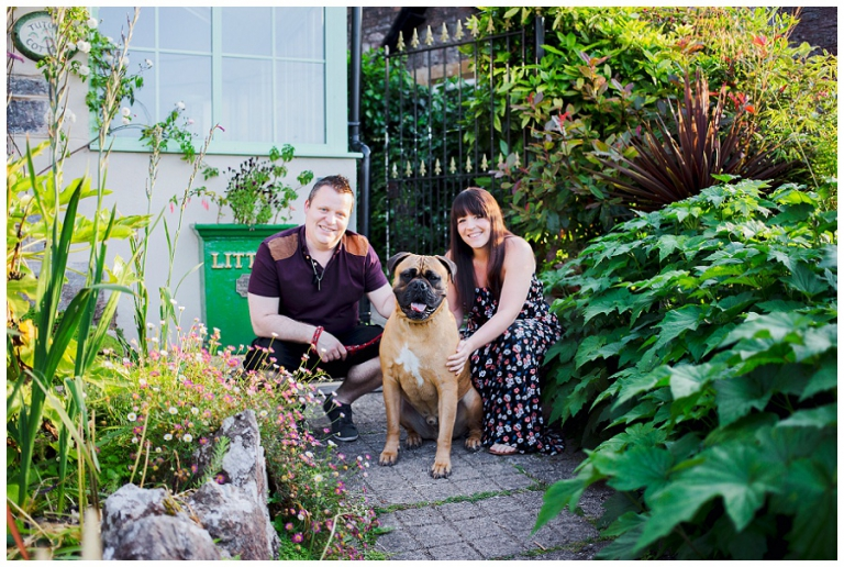 couple posing with their dog outside their home before photography session