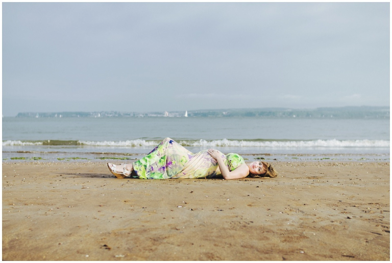 Pregnant woman laying down on sand on Torquay beach by the sea holding her bump