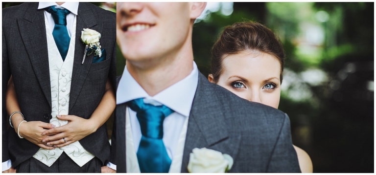 bride with beautiful blue eyes looking over grooms shoulder, holding hime round the waist showing ring and button hole