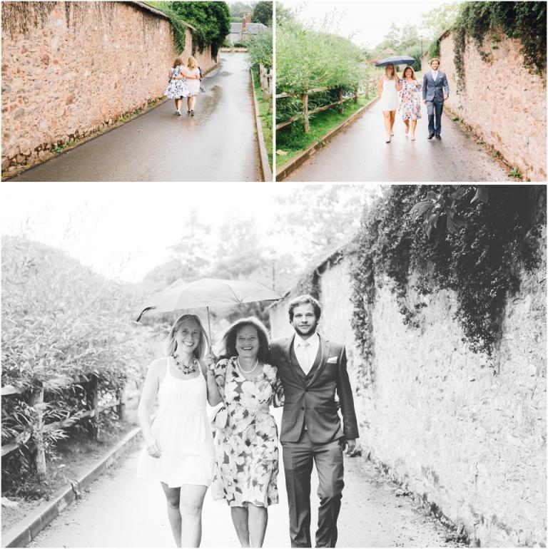cockington-court-torquay-wedding-photography-documentary-style-2-brides-happy-walking-in-rain-under-umbrellas-to-ceremony