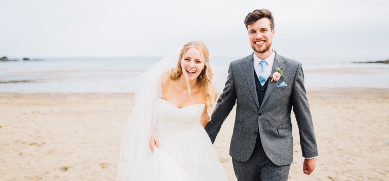 2 Documentary Wedding Photography in Torquay, Exeter, Devon - couple holding hands walking on beach