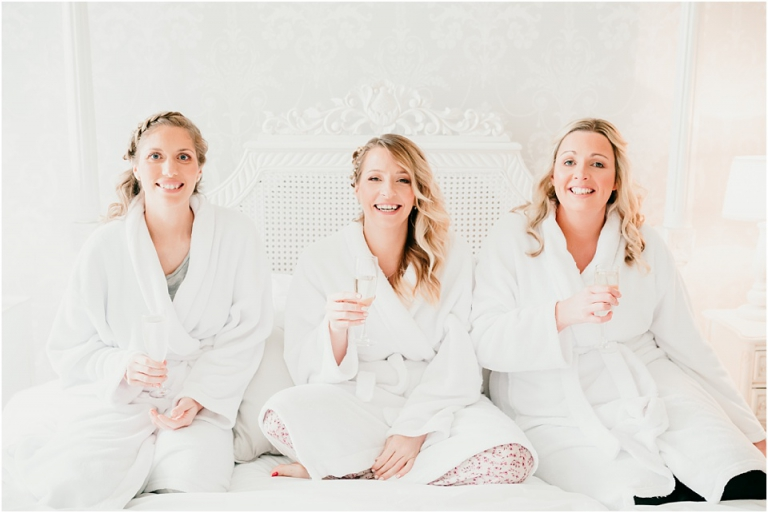 2 Relaxed, Fun, Colourful Wedding at Kingston Estate Devon Wedding Photography - bridesmaids on bed drinking champagne